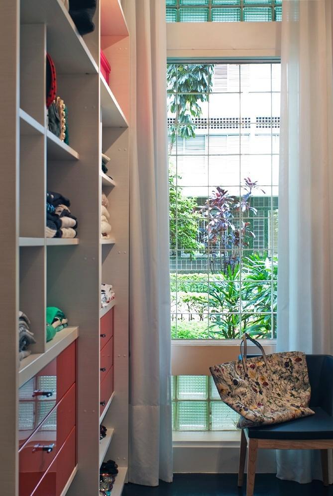 Um closet com marcenaria Florense e cadeira em madeira com encosto de couro sintético (Marché Art de Vie) integra a suíte do casal de publicitários, donos do Apartamento Higienópolis, em São Paulo. Arquitetura e interiores da D2N