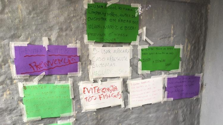 Cartazes na entrada da associação falam em prevenção contra o vírus - Fabiana Batista/UOL