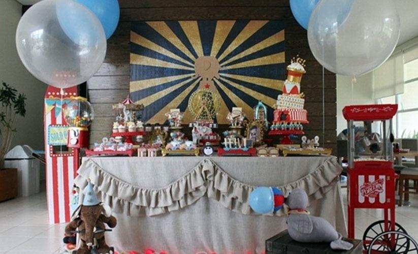 Nesta festa de um ano, a mesa do bolo foi coberta por uma toalha de linho com babados. Animais de tecido, como elefante e foca, ajudaram a remeter ao clima circo de antigamente