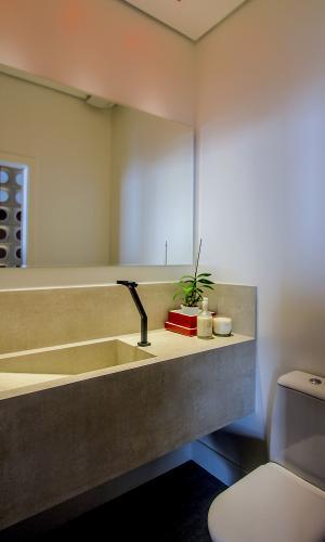 O lavabo conta com cuba e bancada com aspecto rústico, em concreto. Para o ambiente foi escolhida uma iluminação indireta. O projeto de interiores do apê 360°, em São Paulo (SP), é do SP Estudio e Bruno Moraes Arquitetura