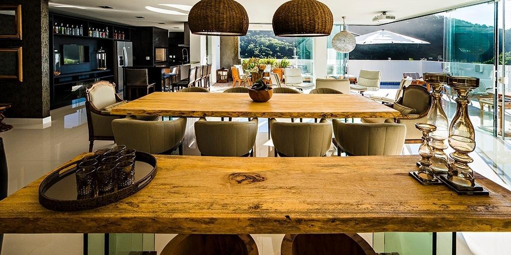 Na sala de jantar desta casa no litoral catarinense, os arquitetos do EB Arquitetura combinaram elementos rústicos - como a mesa de madeira e os pendentes de fibra trançada - aos móveis sofisticados fornecidos pela Sierra e pela Héstia Importadora