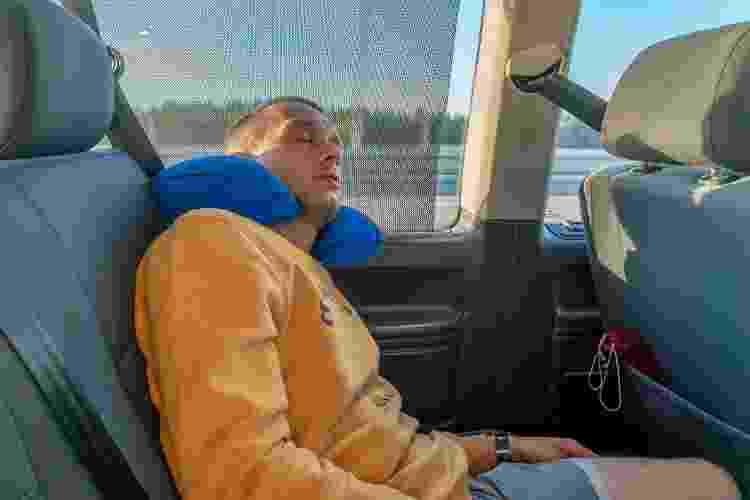 Usar o travesseiro de viagem no pescoço, de forma invertida, pode garantir maior estabilidade durante o sono - Getty Images - Getty Images