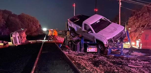 Trem acerta caminhão-cegonha e impacto faz carros saírem voando; assista
