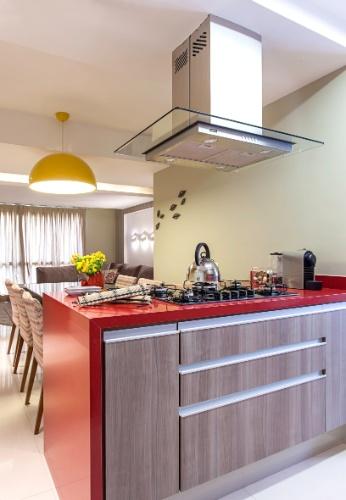 Na cozinha projetada pela arquiteta Cristiane Schiavoni, a bancada vermelha com cooktop está ligada a uma mesa de jantar com seis lugares. A integração do cômodo com o living permite fácil circulação entre os ambientes e favorece o convívio na área comum