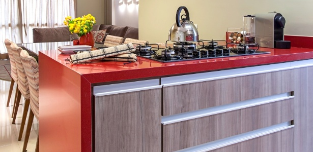 Na cozinha projetada por Cristiane Schiavoni, a bancada vermelha com cooktop está ligada a uma mesa de jantar - Carlos Piratininga/ Divulgação