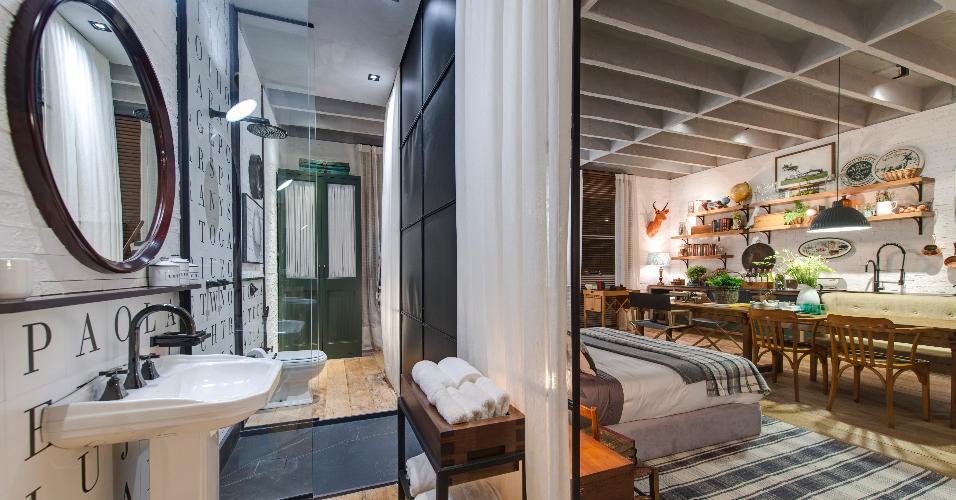 O banheiro pequeno do Loft de Campo, criado por Paola Ribeiro, está parcialmente ligado ao restante da casa e é dividido pelo meio-boxe de vidro. De um lado, fica o vaso sanitário, do outro, o lavatório do tipo coluna, com os metais pretos da Deca. Destaque para os acabamentos e detalhes decorativos, como o espelho circular