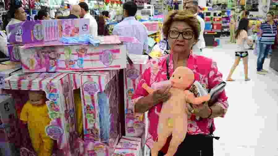 Mulher segura boneca trans, criticada por paraguaios e turistas de Ciudad del Este, no Paraguai - AFP