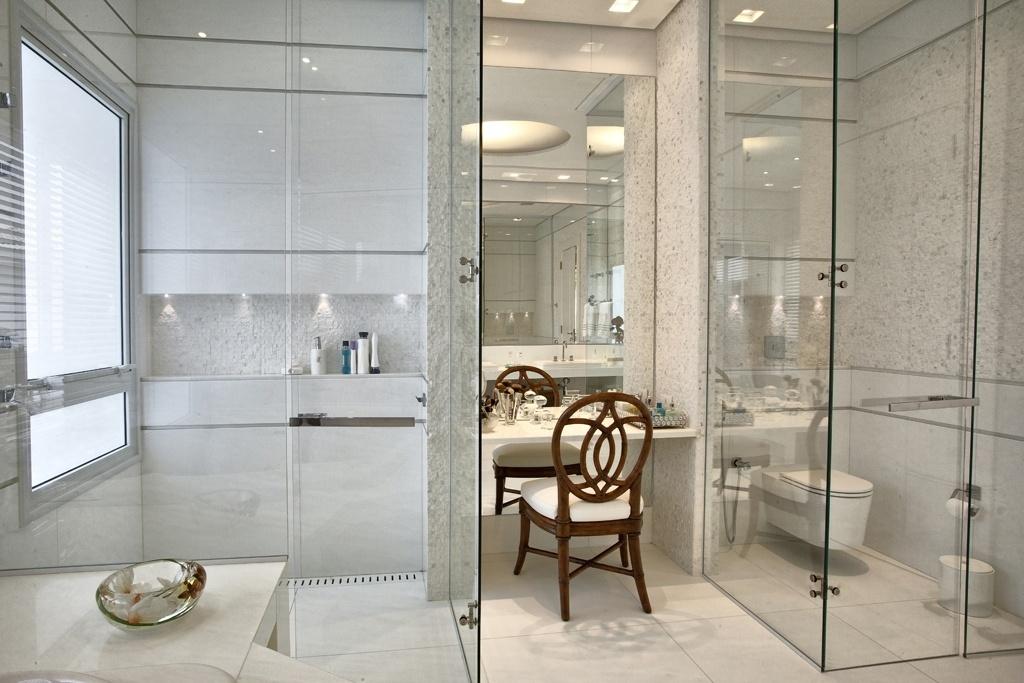 A sala de banho da suíte master, na casa Acapulco, conta com cinco ambientes distintos: na foto é possível ver o boxe com ducha, a bancada para maquiagem (centro) e o sanitário. A setorização é dada pelas caixas de vidro, que impedem a interferência de vapor e odores. A estrutura também torna-se fosca quando um interruptor é acionado e, assim, garante a privacidade de uso. Os interiores foram desenvolvidos pela designer Bianka Mugnatto