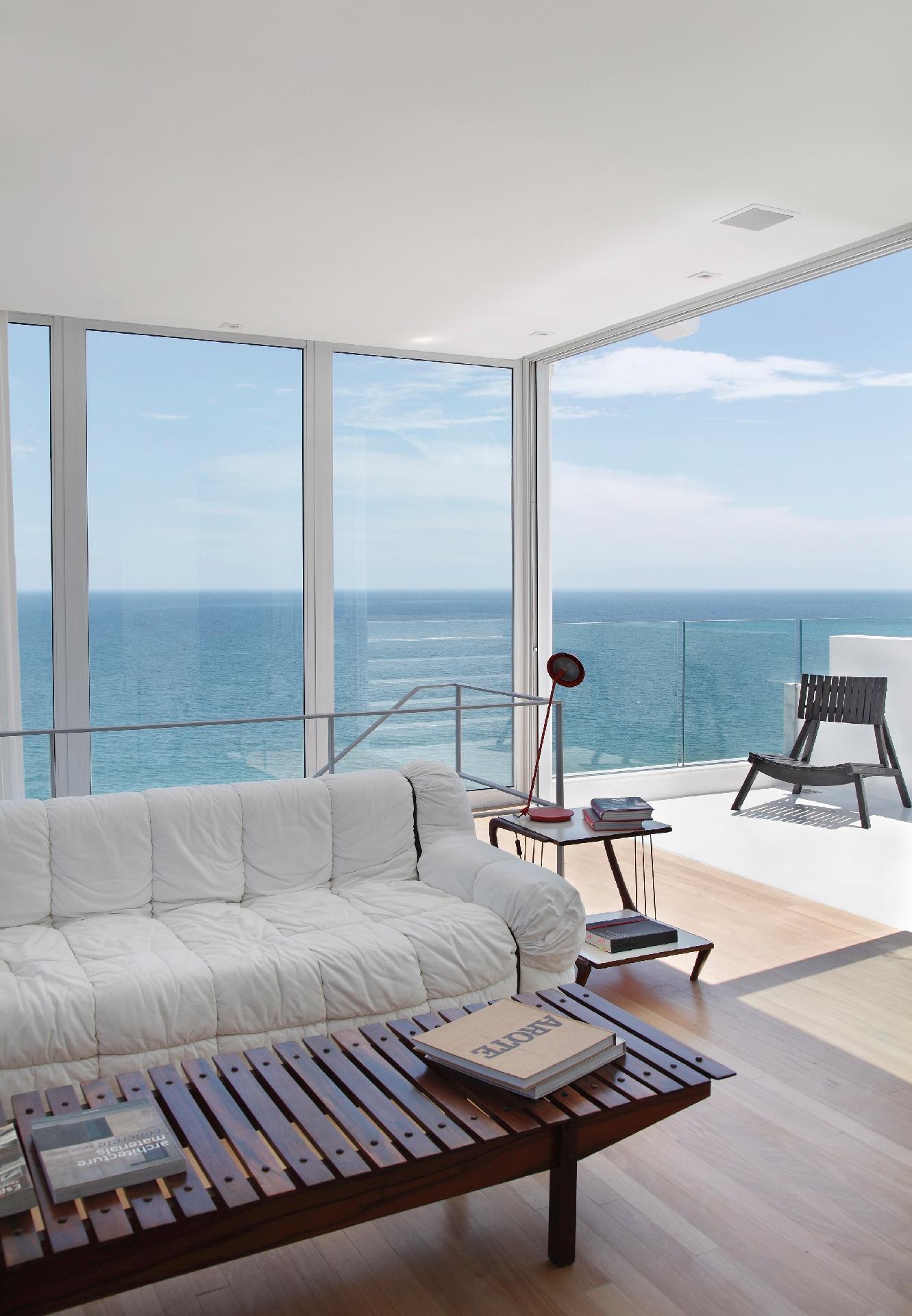 No terceiro pavimento do apartamento, no bairro de Ipanema no Rio de Janeiro (RJ), o escritório InTown projetou uma sala de estar com paredes de vidro. O ambiente com vista para o mar é decorado com o sofá branco Strips (Forma), uma peça de 1972 da arquiteta italiana Cini Boeri, e o banco em jacarandá assinado por Sergio Rodrigues