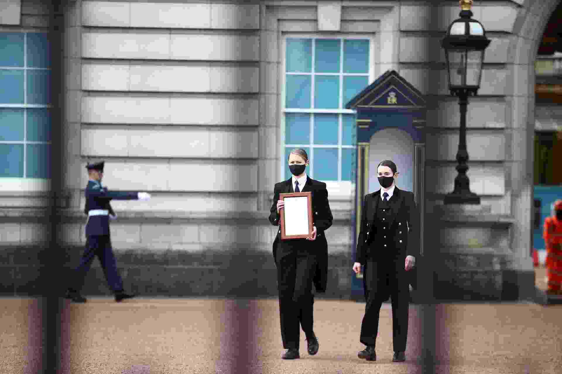 Membros da equipe trazem aviso da morte do príncipe Philip para a cerca do Palácio de Buckingham - HANNAH MCKAY / HANNAH MCKAY