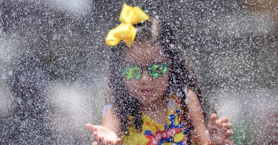 6.fev.2016 - Com o sol forte, foliões se molham durante passagem dos trios infantis no circuito Campo Grande