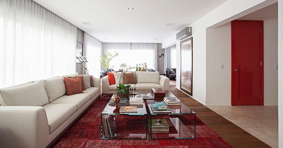 No living, que fica integrado ao home theater e à sala de jantar, o tapete vermelho de retalhos persas (By Kamy) recobre o piso de madeira de demolição e combina com o tom vibrante da porta de entrada