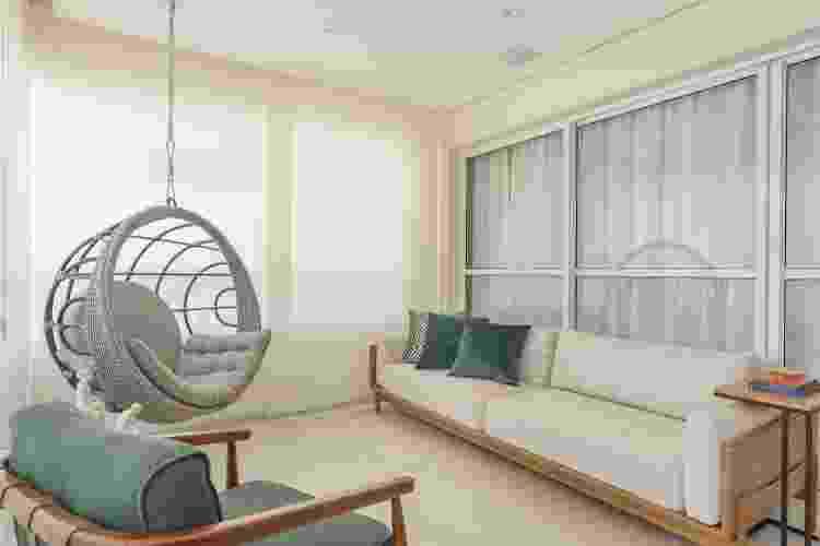 A combinação entre a poltrona suspensa, o sofá e a outra poltrona verde, tornam essa varanda um espaço ideal para receber e relaxar - Henrique Ribeiro - Henrique Ribeiro