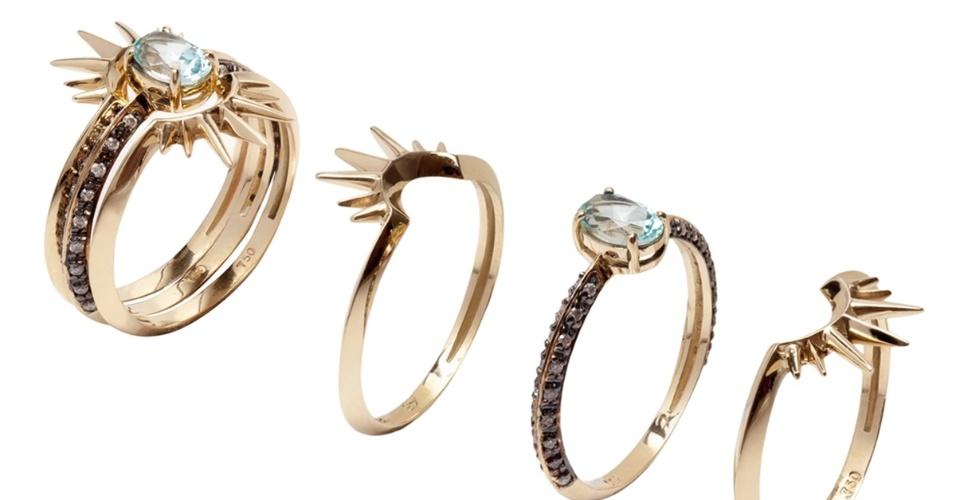 Conjunto com três anéis em ouro amarelo, sendo o central com pedra turquesa, brilhantes brancos e negros. Da Epiphanie.