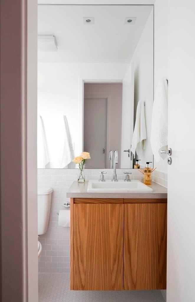 No banheiro social do apê Cátia, as louças foram mantidas. O gabinete tem revestimento em carvalho americano e a bancada é de concreto, pré-moldada, e os metais foram trocados por modelos da Deca, no projeto de reforma assinado pelo escritório Iná Arquitetura