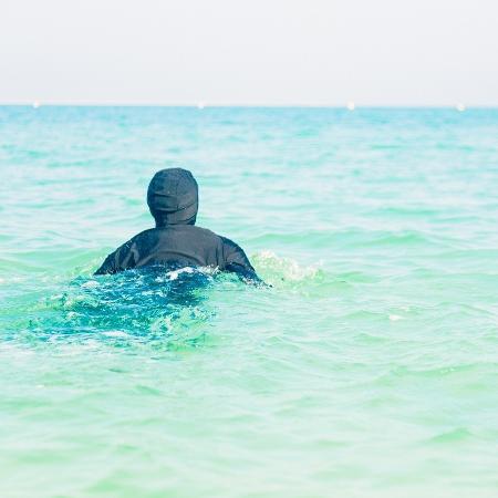 Mulher nada de burkini em praia de Dubai - iStock