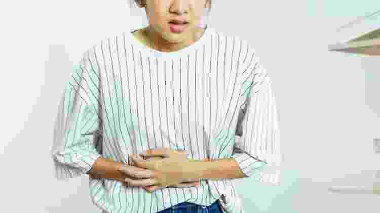 Mulher com cólica, gases, dor de estômago - iStock - iStock