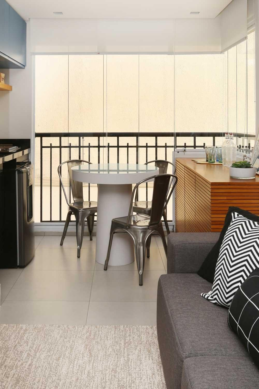 Para aproveitar melhor os 4,7 m² desta varanda, o escritório Bianchi & Lima decidiu integrar o espaço à sala. Com essa solução, foi possível criar um ambiente gourmet pequeno, mas funcional. Nele, há uma bancada com frigobar (à esq.), mesa com três cadeiras e um bufê