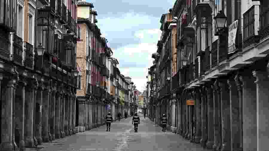 Na cidade de Alcala de Henares, perto de Madri, policiais fazem a ronda em uma rua vazia. Na Espanha, pessoas estão proibidas de sair de casa, exceto para comprar suprimentos essenciais e medicamentos, ou ir ao trabalho - FERNANDO VILLAR/EPA