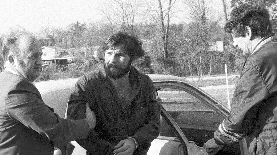 15.11.1974 - Ronald DeFeo Jr. (no centro) chega a julgamento escoltado por policiais - NY Daily News via Getty Images