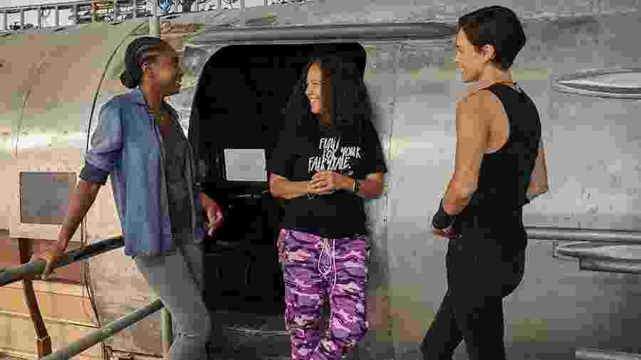 """Gina Prince-Bythewood entre as atrizes Kiki Layne e Charlize Theron nos bastidores de """"The Old Guard"""" - Divulgação"""
