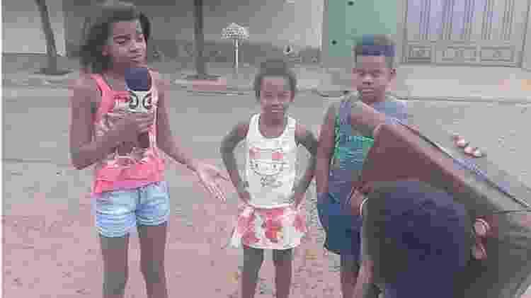 Mirella e os irmãos brincam de fazer um telejornal e mostram problemas do bairro onde vivem, em Ribeirão Preto - Amanda Sales/Reprodução BBC - Amanda Sales/Reprodução BBC