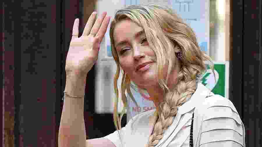 A atriz americana Amber Heard acena ao chegar para depor na Suprema Corte, em Londres - JUSTIN TALLIS/AFP