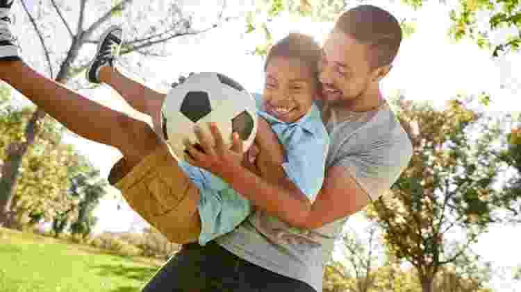 Pai e filho brincando, jogando bola, futebol - iStock - iStock