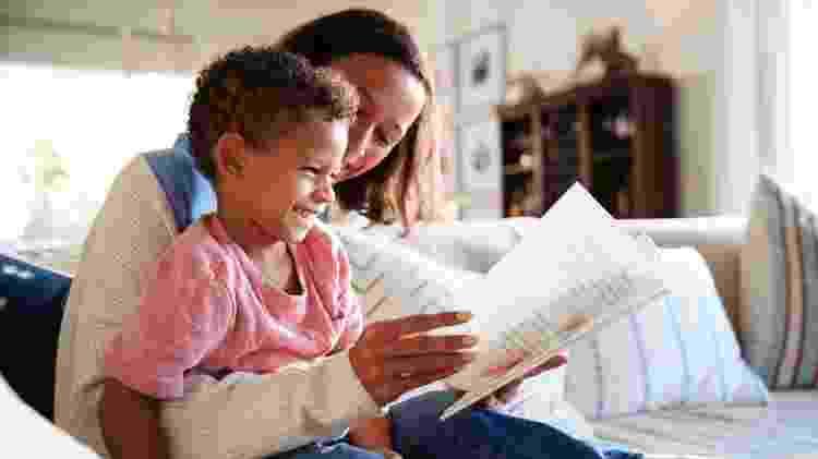 Mãe lendo livro para criança - iStock - iStock