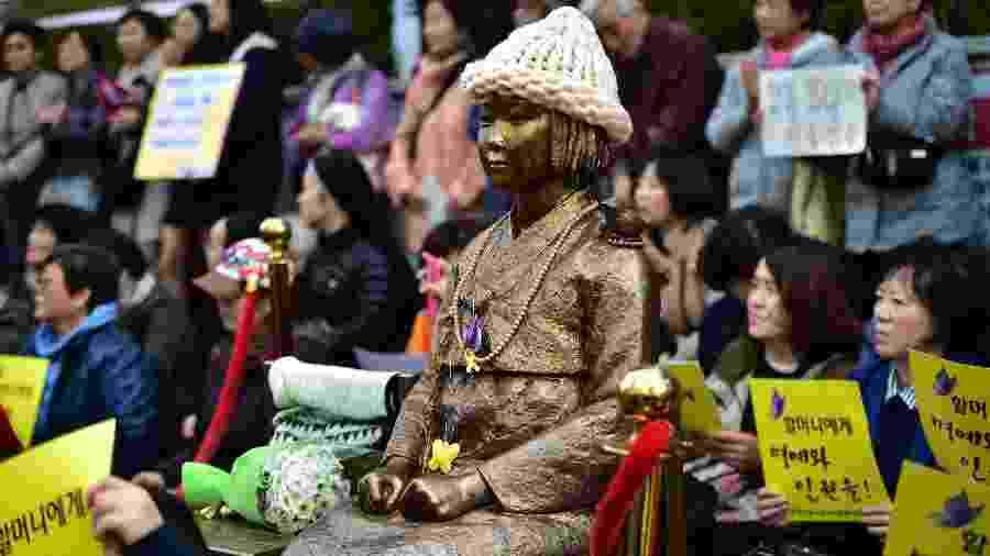 Protestantes se sentam ao lado da estátua de uma jovem sul-coreana, símbolo da lembrança das mulheres forçadas a servirem como escravas sexuais para solados japoneses durante a 2ª Guerra Mundial - AFP