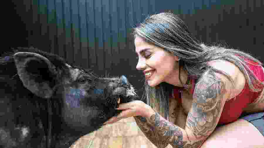 Vanessa Mesquita com o xodó da casa: o porco João, que vive com ela desde filhote  - Keiny Andrade/UOL