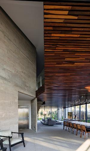 Deste ângulo é possível observar a beleza do volume dos dormitórios, no piso superior, revestido com ripas de madeira. O bloco contrasta com a parede de concreto e aquece o 'living' sob si. A Casa Braga tem projeto do arquiteto Gustavo Penna