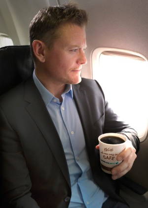 """Foto promocional da WestJet mostra homem com o café do McDonald""""s em avião - Divulgação/CNW Group-WestJet"""