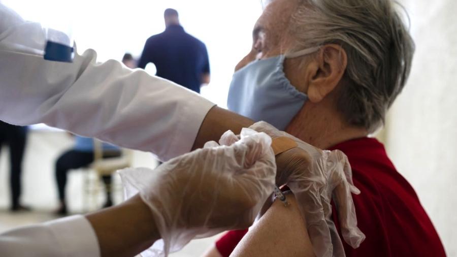 Idosa recebe uma vacina Pfizer-BioNtech Covid-19 de um profissional de saúde no The Palace, uma comunidade independente para idosos, em Coral Gables, em Miami, Flórida, Estados Unidos em 12 de janeiro de 2021 - Anadolu Agency/Colaborador Getty Images