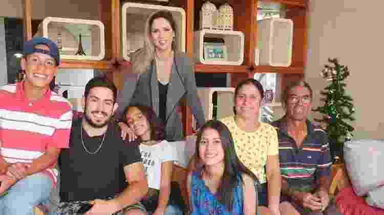 A vendedora Adriana dos Santos (sentada, a segunda da esq. para a dir.) com a família em foto recente - Arquivo pessoal