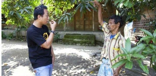 Mulyadi usa o rosto e as mãos para se comunicar com moradores deficientes - BBC