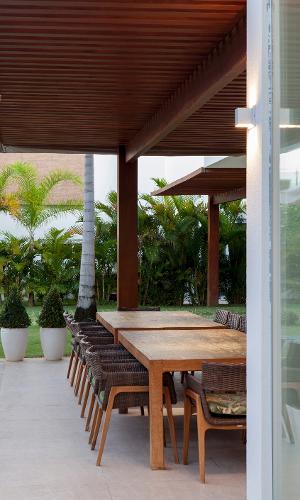 Na varanda, o arquiteto uniu duas mesas de madeira que acomodam 14 cadeiras. Assim, os moradores conseguem recepcionar seus convidados com conforto. A casa de praia fica na cidade de Camaçari (BA) e é assinada por Sidney Quintela