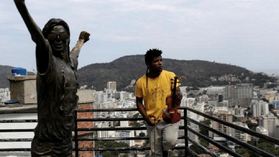 Paulo Maurício Dias posa para foto segurando seu violino ao lado da estátua de Michael Jackson na favela Santa Marta, no Rio - Bruno Kelly/Reuters