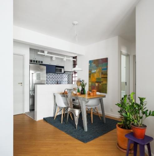 A integração da cozinha com o living é o ponto alto da reforma projetada pela arquiteta Marcela Madureira para o apê Caravelas. O espaço de jantar é composto de mesa retrátil, da Oppa, com espaço para para seis comensais e luminárias (régua sobre a bancada e pendente) da Reka