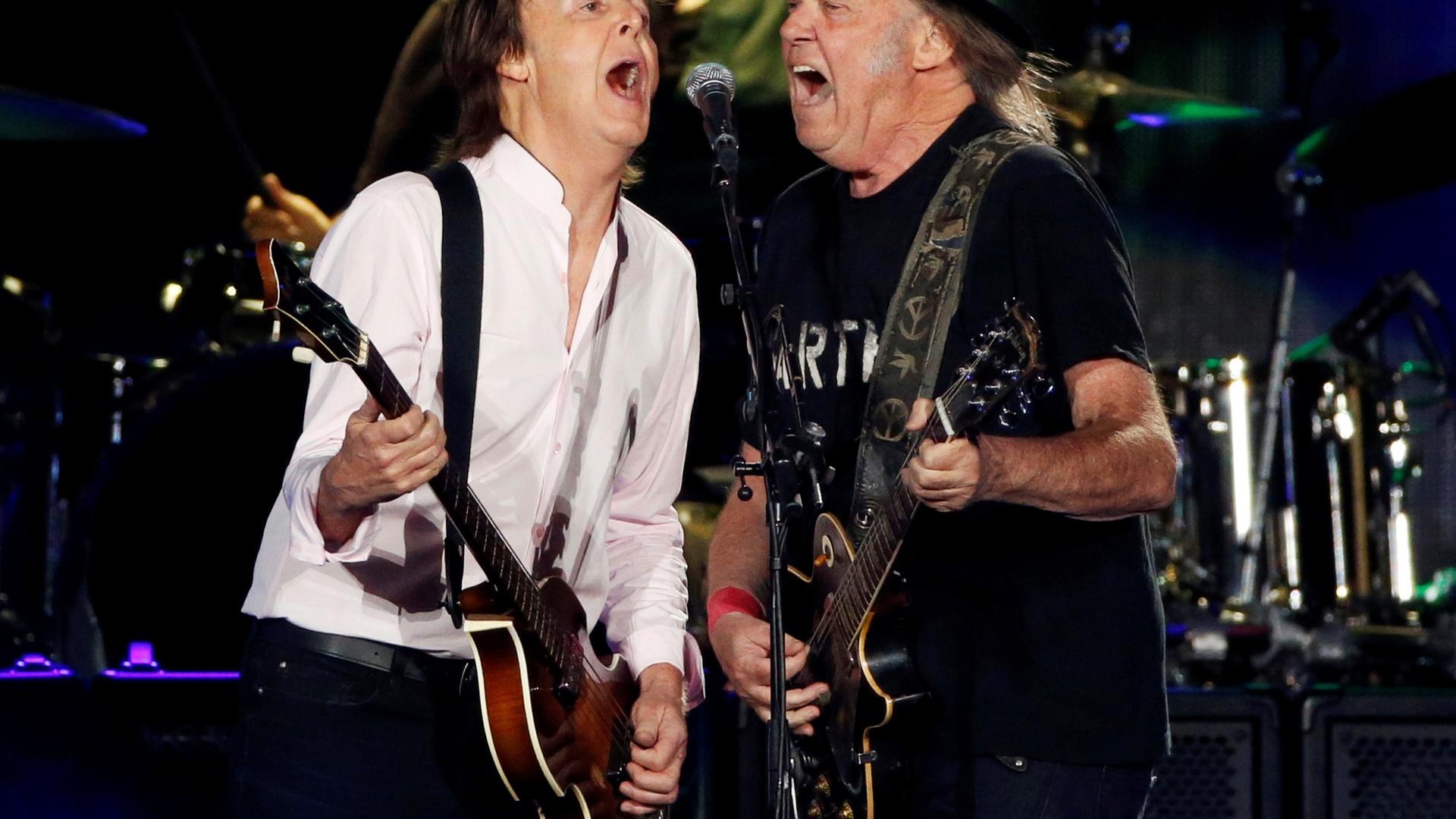 8.out.2016 - Paul McCartney recebe Neil Young no palco durante seu show no Desert Trip, megafestival que reuniu os maiores nomes do rock na cidade de Indio, na Califórnia