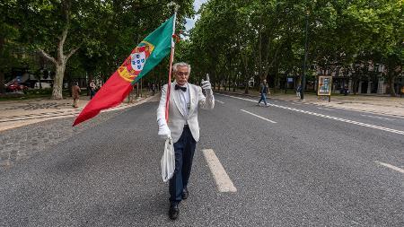 Carlos Alberto Ferreira, de 72 anos, carrega solitário a bandeira de Portugal na Avenida Liberdade durante a celebração da Revolução do Cravos - Corbis/Getty Images
