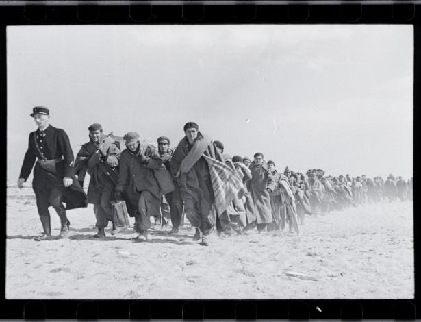Robert Capa  [Refugiados andando na praia. Campo de internação francês para exilados  republicanos, Le Barcarès, França. Março de 1939.] - © International Center Of Photography / Magnum  Collection International Center of Photography