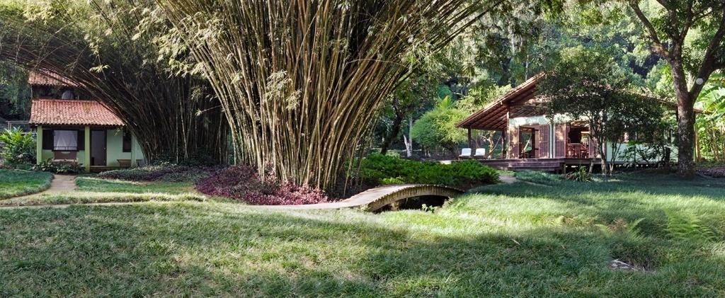 Em um sítio localizado na Ilha Grande (RJ), a junção de dois terrenos deu lugar a um jardim que integra e faz a comunicação entre as casas da propriedade por caminhos de pedra, pontes e grama preta (Ophiopogon japonicus), também conhecida como grama japonesa ou pelo-de-urso. O bucólico jardim é uma criação da arquiteta e paisagista Tania Manela Kurc, que levou o Prêmio Casa Claudia Design de Interiores em 2015, na categoria
