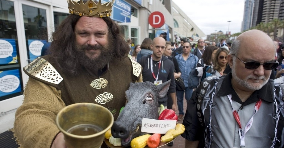"11.jul.2015 - Com um javali morto e um copo de bebida, Dallas Bloom, fã de ""Game of Thrones"", revive o rei Robert Baratheon durante o terceiro dia da Comic-Con 2015"