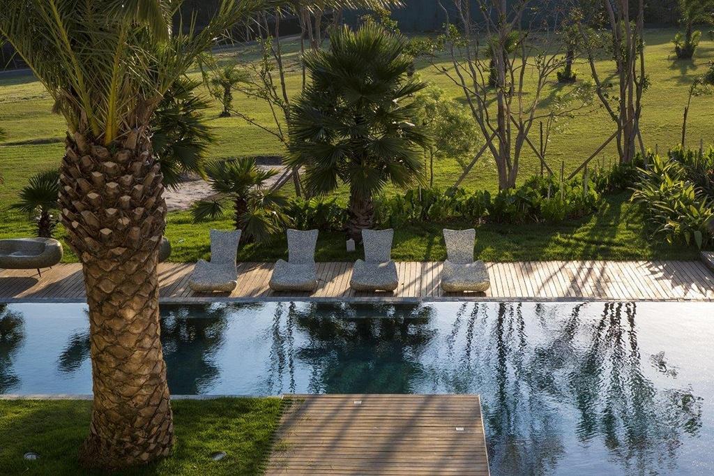 A piscina em L é um elemento chave, que garante o clima de relaxamento e tranquilidade pedido pelos moradores e que ajuda a conectar os interiores aos jardins. Em destaque, sobre o deck, estão as espreguiçadeiras em pastilha de vidro importadas da Tailândia. O projeto de arquitetura e de interiores é de Léo Shehtman