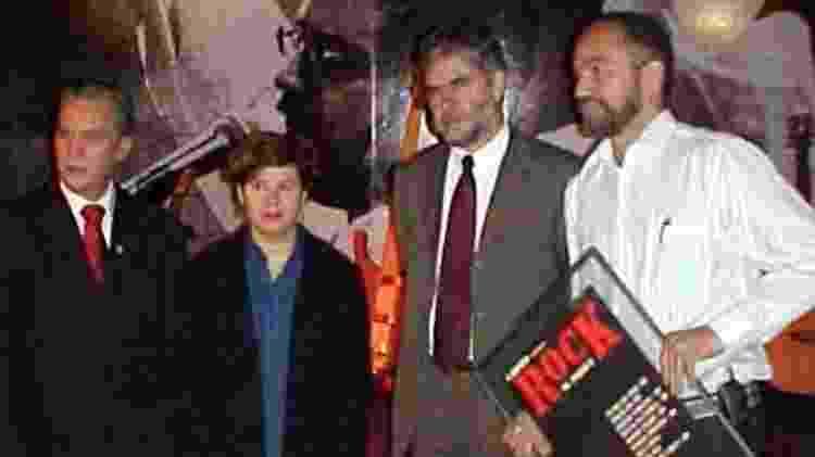 Carlos Alberto Xaulim (segurando o quadro) entrega para Carmem Manfredini, irmã de Renato Russo, uma cópia do cartaz do primeiro show do Legião Urbana - Divulgação - Divulgação