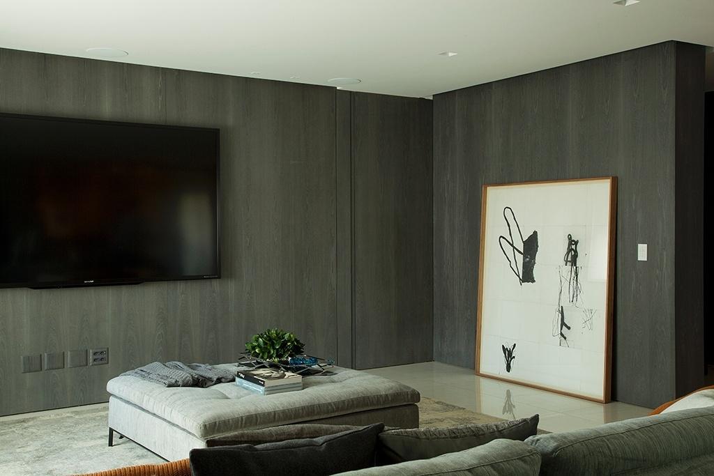 A madeira foi utilizada extensivamente nesse apartamento projetado pela arquiteta Consuelo Jorge em São Paulo. O material veste as paredes de forma elegante e é valorizado pela iluminação embutida em rasgos no forro de gesso