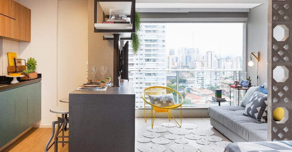 Feito de crochê, o tapete quebra a rigidez de formas e tecidos deste pequeno apartamento. Além disso, a brincadeira de círculos combina com a parede de elementos vazados entre a sala e o quarto. Ideia da doob arquitetura