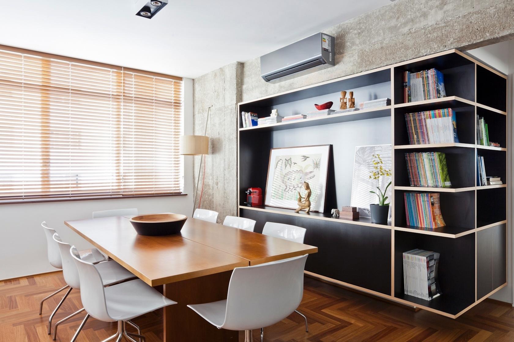 A sala de jantar do apartamento de 160 m2 no Paraíso, zona sul de São Paulo, recebeu uma divisória estante revestida com laminado melamínico, que junto do tampo da mesa de jantar foi desenvolvida no próprio escritório do arquiteto Renato Dalla Marta, do AUM Arquitetos. O arquiteto também manteve vigas e pilares de concreto aparentes e revestiu o piso com assoalho de cumaru