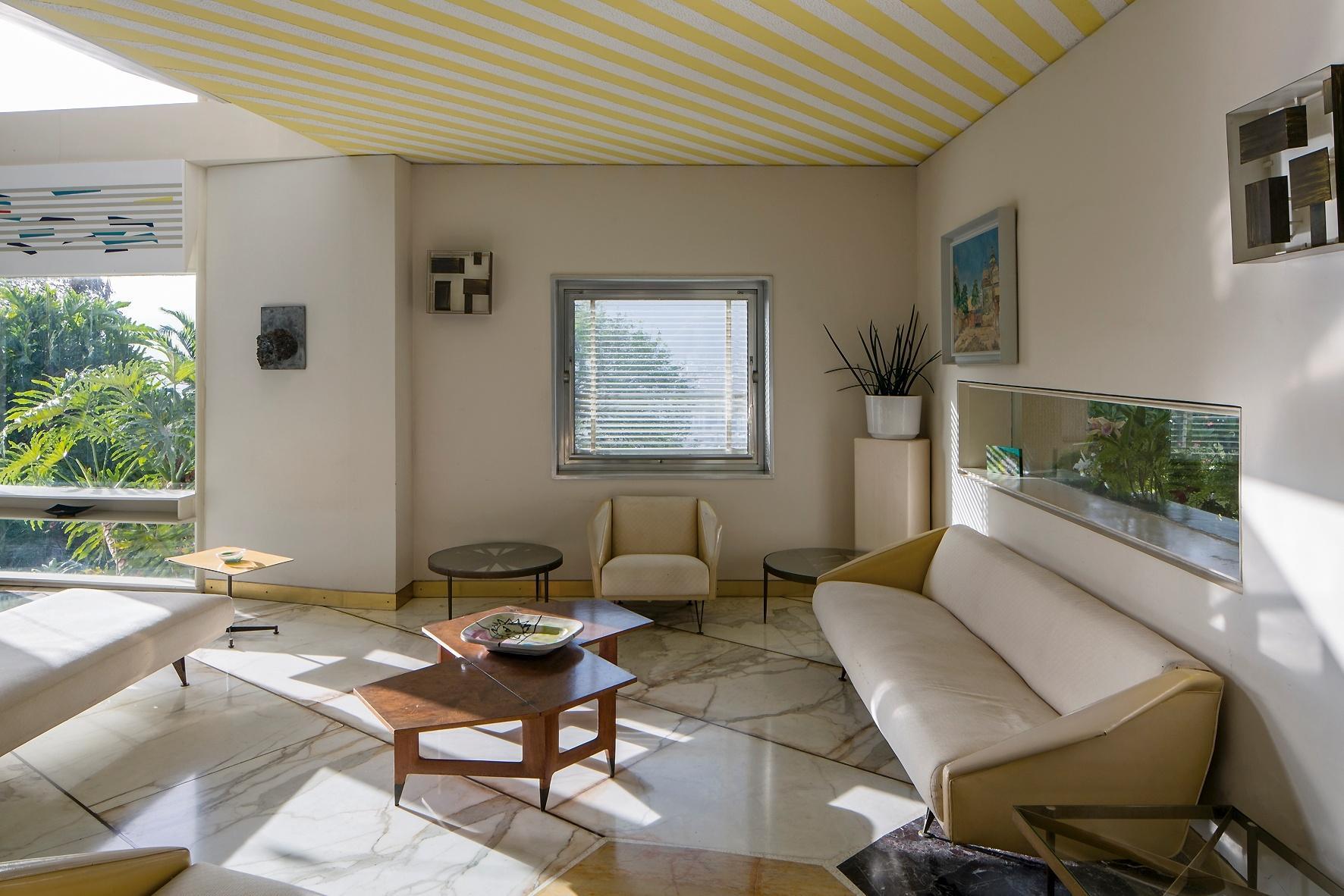 No estar da Villa Planchart chamam a atenção a janela-vitrine (sobre o sofá), o piso de mármore colorido e o teto com listras brancas e amarelas. A casa foi projetada pelo arquiteto italiano Gio Ponti, na Venezuela, e se propõe a conciliar arquitetura, mobiliário e os objetos pessoais dos antigos moradores